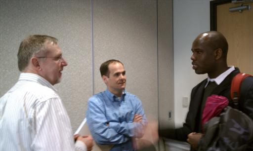 Peter Veit of WRI, Johnny Wilson of TNC and Emmanuel Sulle of University of Maryland talk after the meeting