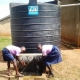 Students at Karongo Primary school washing their hands at the newly installed water tank at their school